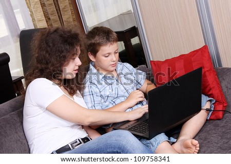 Happy children with a laptop on a sofa - stock photo