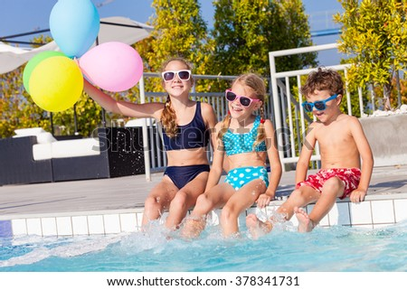 happy children with balloons playing on the swimming pool at the day time. Concept of friendly family. - stock photo