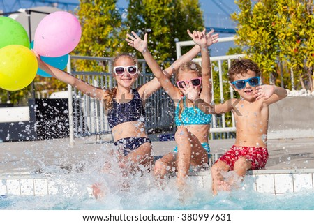 happy children with balloons playing on the swimming pool at the day time. Concept of friendly family.