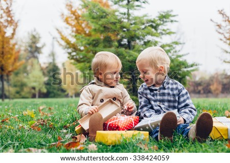 Happy children with gift in the park - stock photo