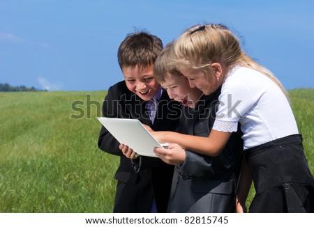 happy children with laptop, outdoor - stock photo