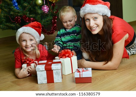 happy children with mother near Christmas tree