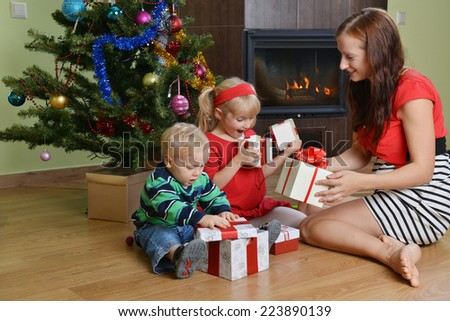 happy children with mother sitting near Christmas tree - stock photo