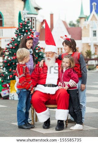 Happy children with Santa Claus against Christmas tree in courtyard