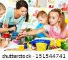 Happy children  with teacher painting. - stock photo