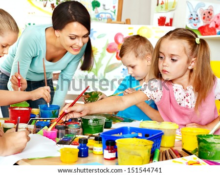 Happy children  with teacher painting.