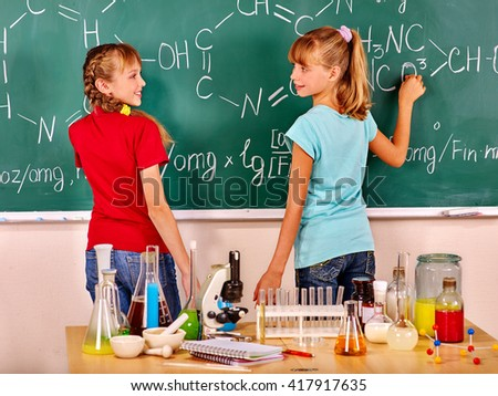 Happy children writing on blackboard  in chemistry class.Focus on  table with flasks. - stock photo
