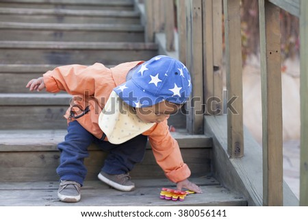Happy Chinese baby boy playing on stairs outdoors, shot in Beijing, China - stock photo
