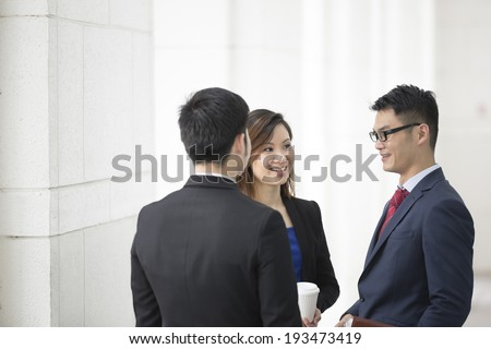 Happy Chinese Business colleagues outside the office talking to each other. - stock photo