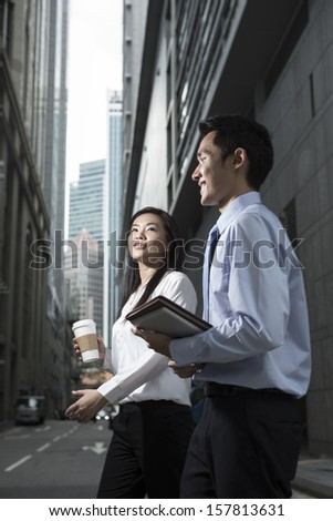 Happy Chinese Business colleagues walking outside office & talking to each other. - stock photo