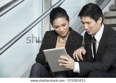 Happy Chinese Business man and woman looking at a digital tablet.