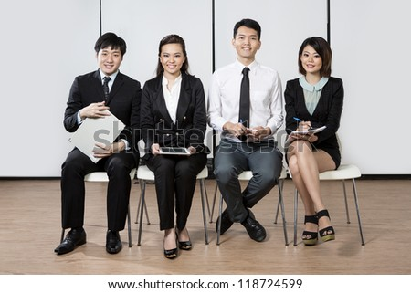 Happy Chinese business team sitting in a row at office. - stock photo