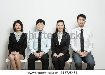Happy Chinese business team sitting in a row at office.