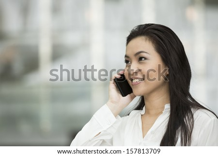 Happy Chinese Businesswoman talking on smart phone. - stock photo