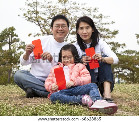 Happy chinese family holding red envelop celebrating chinese new year - stock photo