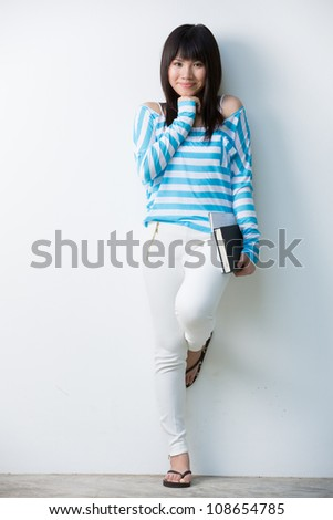 Happy Chinese female student leaning against a wall with a books - stock photo