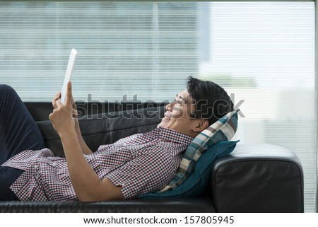 Happy Chinese man at home on sofa using a digital Tablet PC. - stock photo