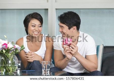 Happy Chinese man giving a present to his girlfriend at home in their living room