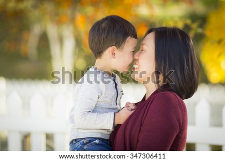 Happy Chinese Mom Having Fun and Holding Her Mixed Race Little Boy. - stock photo