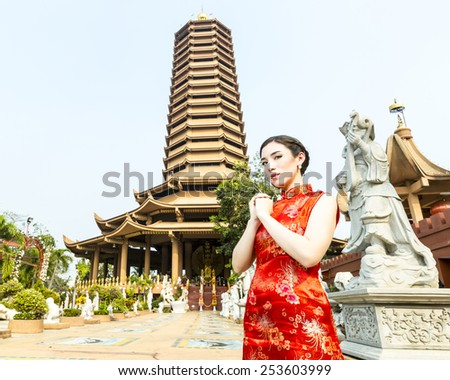 Happy Chinese new year. Asian woman with gesture of congratulation and the chinese temple background - stock photo