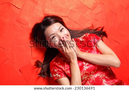 happy chinese new year. Smile woman lying on red envelope bed, high angle view - stock photo