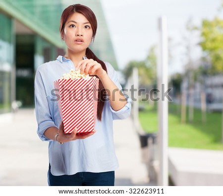 happy chinese woman with popcorn - stock photo