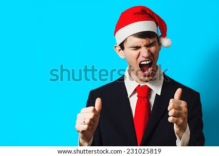 Happy christmas businessman in santa hat with thumb up on a blue background - stock photo