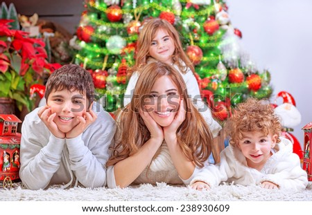 Happy Christmas celebration, cheerful family having fun at home, lying down near beautiful decorated Christmas tree, love and happiness concept - stock photo