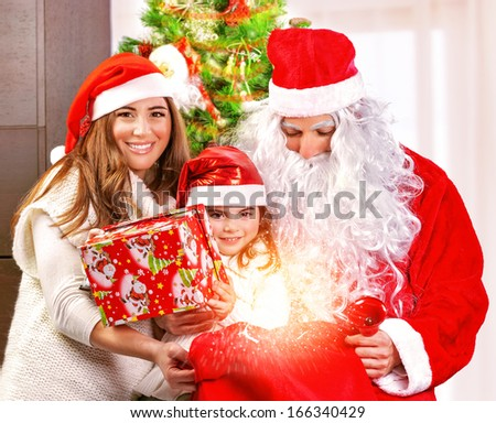 Happy Christmas celebration, cheerful parents give festive gift to adorable sweet child, wearing Santa Claus costume, New Year party concept - stock photo