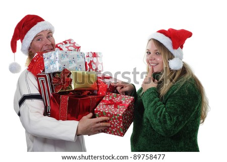 Happy Christmas couple piling gifts into their arms - stock photo