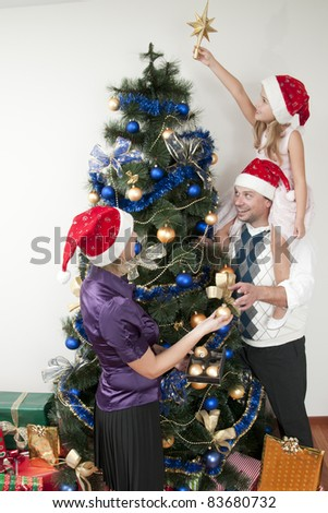 Happy Christmas - Family decorating a Christmas tree