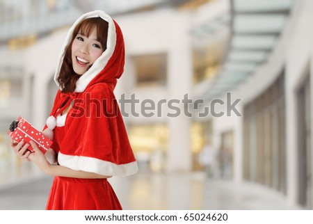 Happy Christmas girl holding gift smiling over department store. - stock photo