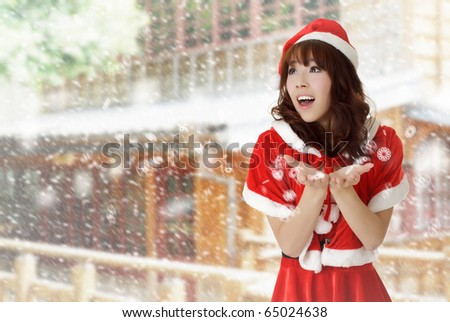 Happy Christmas girl in outdoor with snow falling in winter.