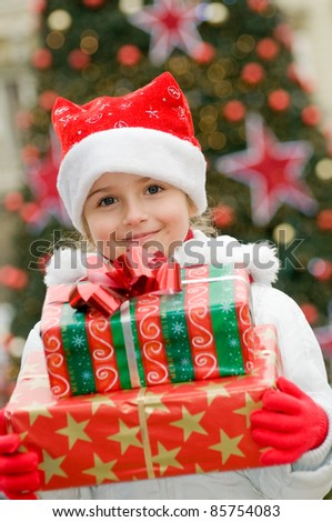 Happy Christmas - Little girl with Christmas gifts portrait - Defocused Christmas Tree Lights - stock photo