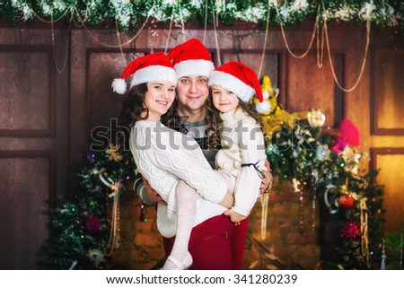 Happy Christmas mother, father and daughter in santa red hats - stock photo