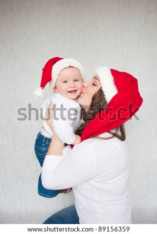 Happy Christmas mother kissing baby son on a white background. - stock photo