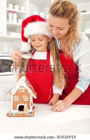 Happy christmas people making gingerbread house - stock photo