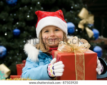 Happy Christmas time - outdoor portrait of cute girl with Christmas gift