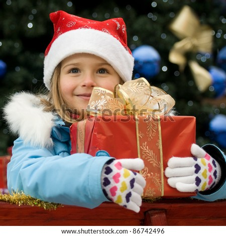 Happy Christmas time - portrait of cute girl in Christmas sledge