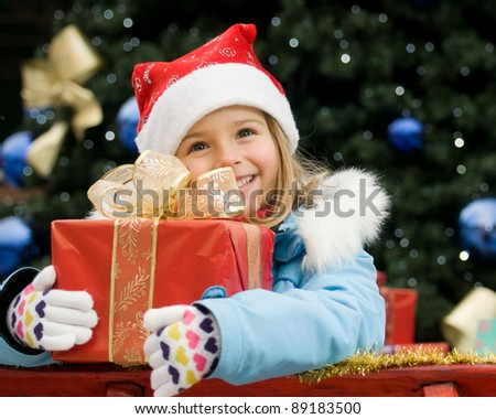 Happy Christmas time - portrait of cute girl in Christmas sledge - stock photo