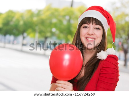 happy christmas woman holding a balloon against a street background