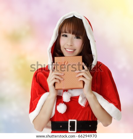 Happy Christmas woman holding gift box over colorful background. - stock photo