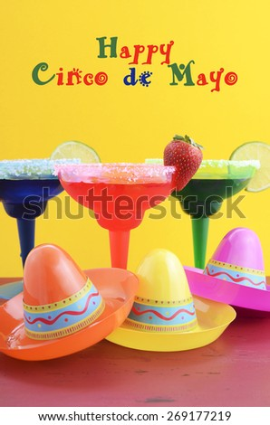 Happy Cinco de Mayo colorful party theme with bright color margarita drinks on red wood table and yellow background.  - stock photo