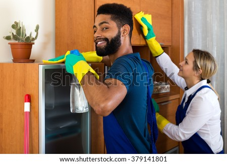 Happy cleaners cleaning and dusting in ordinary house - stock photo
