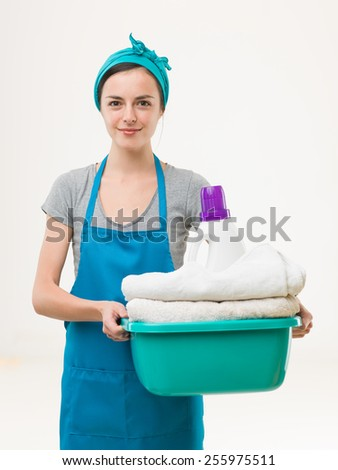 happy cleaning woman holding basin with clean towels and detergent, isolated on white background - stock photo