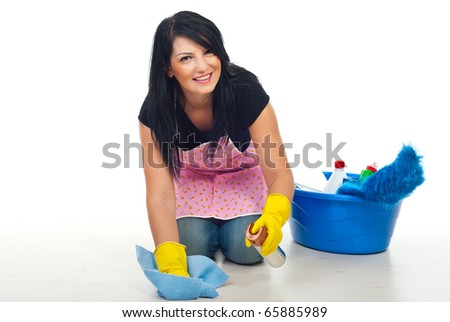 Happy cleaning woman kneel and floor wipe with a dustt cloth  and spray in her house - stock photo