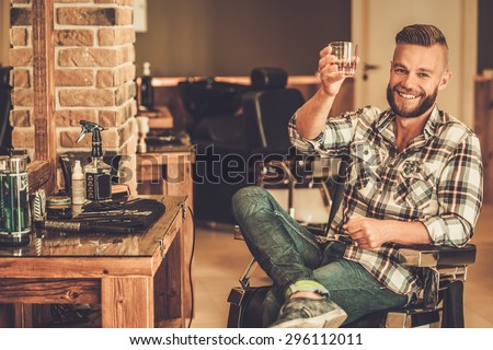Happy client in barber shop will glass of whiskey  - stock photo