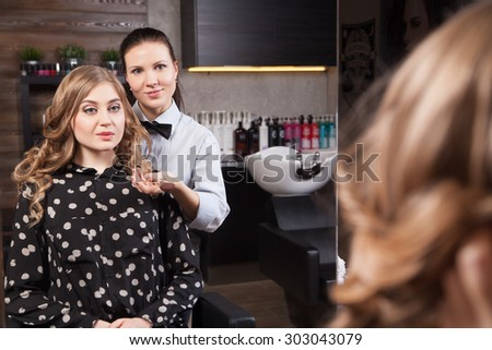 Happy client looking at mirror in salon - stock photo