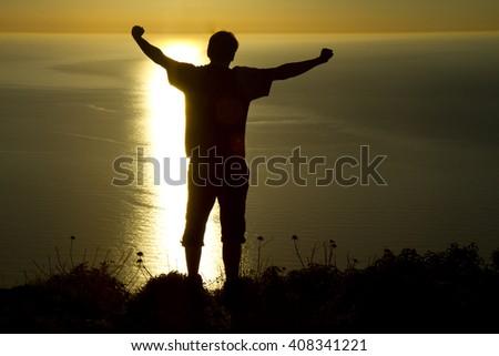 happy climber enjoying the ocean view at sunset - stock photo