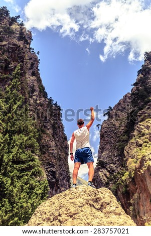 Happy climber hiker or trail cross country runner reaching life goal, success man at summit, business concept. Young runner arms up outstretched, happiness and rock climbing achievement in mountains - stock photo